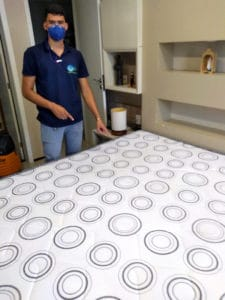 Colaborador mostrando colchão limpo